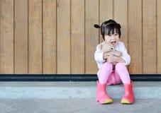 Το πορτρέτο του χαριτωμένου μικρού κοριτσιού κάθεται και αγκαλιάζοντας Teddy αντέξτε ενάντια στον ξύλινο τοίχο σανίδων στοκ φωτογραφίες