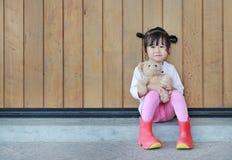 Το πορτρέτο του χαριτωμένου μικρού κοριτσιού κάθεται και αγκαλιάζοντας Teddy αντέξτε ενάντια στον ξύλινο τοίχο σανίδων στοκ φωτογραφία με δικαίωμα ελεύθερης χρήσης
