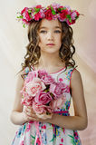 Το πορτρέτο του χαριτωμένου μικρού κοριτσιού στο συμπαθητικό φόρεμα άνοιξη, με το flowery στεφάνι στο κεφάλι, κρατά την ανθοδέσμη στοκ εικόνες