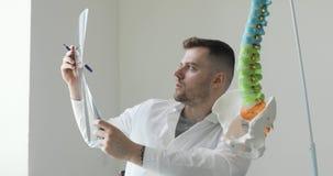 Το πορτρέτο του χειρούργου γιατρών νεαρών άνδρων εξετάζει την των ακτίνων X εικόνα και εξηγεί την ασθένεια στον ασθενή απόθεμα βίντεο