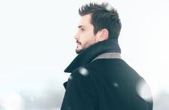 Το πορτρέτο του όμορφου ατόμου μόδας στη χειμερινή χιονοθύελλα κοιτάζει, άποψη σχεδιαγράμματος στοκ εικόνες με δικαίωμα ελεύθερης χρήσης