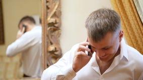 Το πορτρέτο του όμορφου ατόμου, νέος επιχειρηματίας, σε ένα άσπρο πουκάμισο κρατά ένα smartphone, κινητό τηλέφωνο, που μιλά φιλμ μικρού μήκους