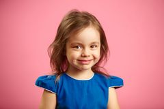 Το πορτρέτο του όμορφου κοριτσιού παιδιών με τη γοητεία κοιτάζει στο μπλε υπόβαθρο στοκ εικόνες με δικαίωμα ελεύθερης χρήσης