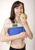 Το πορτρέτο του όμορφου κοριτσιού που φορά τον αθλητισμό ντύνει το κράτημα των κλιμάκων και μιας μετρώντας ταινίας με το πράσινο μ στοκ εικόνα