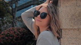 Το πορτρέτο του όμορφου κοριτσιού στα γυαλιά ηλίου είναι χαλάρωση, κλίνοντας σε έναν τοίχο στην οδό πόλεων στην ηλιόλουστη ημέρα απόθεμα βίντεο