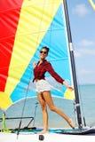 Το πορτρέτο του όμορφου κοριτσιού brunette κρατά τα πανιά και το χαμόγελο βαρκών Στοκ Φωτογραφίες