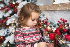 Το πορτρέτο του όμορφου μικρού κοριτσιού εξετάζει ένα παιχνίδι Χριστουγέννων στο σπίτι Στοκ Εικόνες