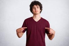 Το πορτρέτο του όμορφου νέου αρσενικού δείχνει στο κενό διάστημα της περιστασιακής μπλούζας για τη διαφήμισή σας ή σχεδιάζοντας τ στοκ φωτογραφία με δικαίωμα ελεύθερης χρήσης
