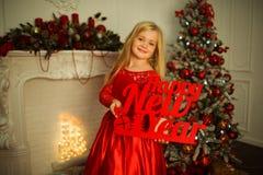 Το πορτρέτο του όμορφου ξανθού κοριτσιού φορά διακοσμημένη φορεμάτων μόδας το κόκκινο πλησίον χριστουγεννιάτικο δέντρο Στοκ Εικόνες