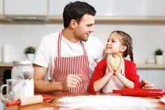 Το πορτρέτο του όμορφου στοργικού πατέρα την αγκαλιάζει λίγη κόρη, κάνει τα μπισκότα μαζί, που είναι στην καλή διάθεση στοκ φωτογραφίες με δικαίωμα ελεύθερης χρήσης