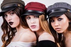 Το πορτρέτο τριών όμορφων, προκλητικών γυναικών, φίλες με το makeup και τη ζωηρόχρωμη ΚΑΠ, καπέλα στο κεφάλι σας, κλείνει επάνω Μ στοκ φωτογραφία με δικαίωμα ελεύθερης χρήσης