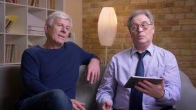 Το πορτρέτο των ανώτερων αρσενικών φίλων που κάθονται μαζί στον καναπέ ανοίγει app στην ταμπλέτα παίρνει ικανοποιημένο απόθεμα βίντεο