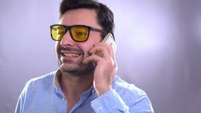Το πορτρέτο των ελκυστικών ευτυχών σύγχρονων νέων σγουρών ατόμων στο ελεγμένο πουκάμισο που μιλά στο κύτταρο τηλεφωνά απόθεμα βίντεο