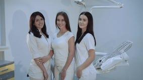 Το πορτρέτο των ευτυχών, βέβαιων οδοντιάτρων εξετάζει τη κάμερα στο οδοντικό δωμάτιο απόθεμα βίντεο
