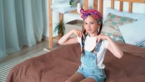 Το πορτρέτο των ευτυχών παιχνιδιών κοριτσιών με τις μακριές πλεξούδες, εξετάζει τη κάμερα, σε αργή κίνηση απόθεμα βίντεο