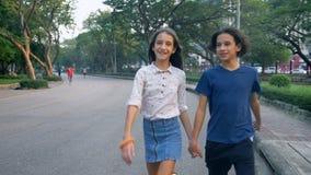 Το πορτρέτο των εφήβων, το αγόρι και το κορίτσι που περπατούν στη φύση σε ένα μεγάλο πάρκο με τα δίδυμα ευχαρίστησης, αδελφών και απόθεμα βίντεο