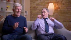 Το πορτρέτο των παλαιών αρσενικών φίλων που προσέχουν τη TV συναντιέται με εξαιρετικά ευτυχές και η ευχαριστημένη αύξηση παραδίδε απόθεμα βίντεο