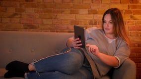 Το πορτρέτο χαλαρωμένος συν το μακρυμάλλες πρότυπο μεγέθους βρίσκεται στον καναπέ που λειτουργεί προσεκτικά με την ταμπλέτα στην  απόθεμα βίντεο