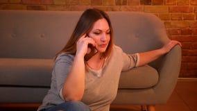 Το πορτρέτο χαλαρωμένος συν τη μακρυμάλλη πρότυπη συνεδρίαση μεγέθους στο πάτωμα μιλά χαρωπά στο smartphone στην άνετη εγχώρια ατ απόθεμα βίντεο