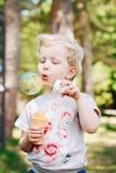 Το πορτρέτο χαριτωμένου αστείος λίγο ξανθό καυκάσιο μικρό παιδί κοριτσιών παιδιών που στέκεται στο πράσινο δασικό φυσώντας σαπούν στοκ εικόνα