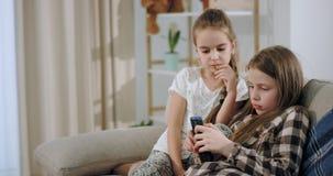 Το πορτρέτο χαριτωμένων δύο αδελφών που παίζουν στο smartphone συγκεντρώθη απόθεμα βίντεο