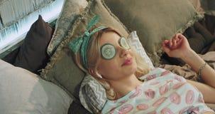 Το πορτρέτο όμορφες νέες κυρίες έχει μια μάσκα ματιών το πρωί στα πρόσωπα αυτή που καθορίζει στο κρεβάτι στις πυτζάμες απόθεμα βίντεο