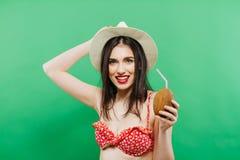 Το πορτρέτο Brunette με το καπέλο κάουμποϋ και μακρυμάλλης στο κόκκινο κοκτέιλ καρύδων εκμετάλλευσης μαγιό σε την παραδίδει το στ Στοκ Εικόνα