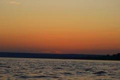 Το πορφυρό ηλιοβασίλεμα στην ευρεία έκταση του ποταμού Στοκ Εικόνες