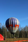 Το πορφυρό μπαλόνι αέρα είναι στον τομέα πριν από την πτήση και το μπλε CL Στοκ φωτογραφία με δικαίωμα ελεύθερης χρήσης