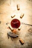Το ποτήρι του κόκκινου κρασιού με βουλώνει και ένα ανοιχτήρι Στοκ Εικόνες