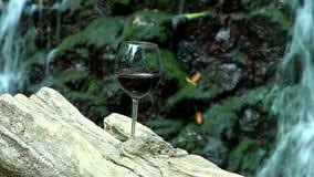 Το ποτήρι του κόκκινου κρασιού στέκεται σε μια ξύλινη επιφάνεια στο υπόβαθρο έναν βράχο με έναν καταρράκτη απόθεμα βίντεο