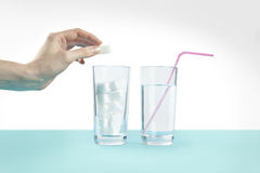 Το ποτήρι του νερού ενάντια στη ζάχαρη, ασθένεια διαβήτη, γλυκός εθισμός, χέρι ρίχνει μια ζάχαρη Στοκ Εικόνες
