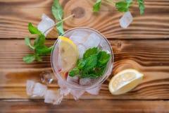 Το ποτήρι του νερού με το λεμόνι και τη μέντα εξυπηρέτησε με τους κύβους πάγου σε έναν ξύλινο πίνακα Στοκ Εικόνες