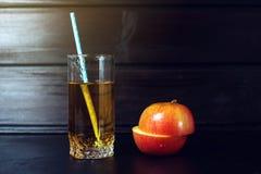Το ποτήρι του χυμού της Apple με την τεμαχισμένη Apple είναι στο σκοτεινό ξύλο Στοκ φωτογραφία με δικαίωμα ελεύθερης χρήσης