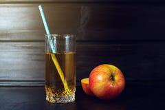 Το ποτήρι του χυμού της Apple με την τεμαχισμένη Apple είναι στο σκοτεινό ξύλο Στοκ Φωτογραφίες