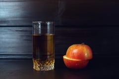 Το ποτήρι του χυμού της Apple με την τεμαχισμένη Apple είναι στο σκοτεινό ξύλο Στοκ Εικόνες