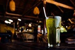Το ποτό με τον πάγο στο φλυτζάνι γυαλιού στέκεται στον πίνακα στο θερινό καφέ υποβάθρου Στοκ Φωτογραφίες