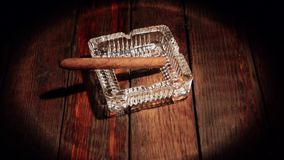 Το πούρο βρίσκεται ashtray σε έναν ξύλινο πίνακα Φωτισμένος από το επίκεντρο απόθεμα βίντεο