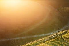 Το ποδήλατο βουνών είναι στο λόφο με την πράσινη χλόη στο υπόβαθρο ηλιοβασιλέματος Στοκ Φωτογραφίες
