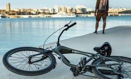 Το ποδήλατο βρίσκεται στην αποβάθρα δίπλα σε έναν νεαρό άνδρα απολαμβάνει τη θέα της φύσης, οπισθοσκόπο στοκ φωτογραφίες