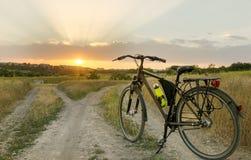 Το ποδήλατο στέκεται σε έναν του χωριού δρόμο που διαιρείται σε μέρη χρόνος ηλιοβασιλέματος απόμακρων πιθανοτήτων έκθεσης Στοκ Εικόνα