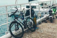 Το ποδήλατο στέκεται σε μια αποβάθρα στα πλαίσια ενός πλέοντας γιοτ στο κυανό θαλάσσιο νερό στοκ φωτογραφία
