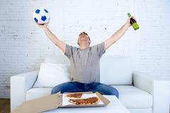 Το ποδοσφαιρικό παιχνίδι προσοχής σφαιρών εκμετάλλευσης νεαρών άνδρων στη TV ξαπλώνει στο σπίτι με την πίτσα και την μπύρα γιορτά Στοκ εικόνα με δικαίωμα ελεύθερης χρήσης