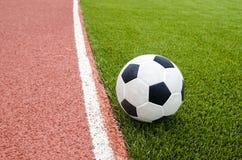 Το ποδόσφαιρο είναι στο τεχνητό γήπεδο ποδοσφαίρου χλόης στο στάδιο Στοκ φωτογραφίες με δικαίωμα ελεύθερης χρήσης
