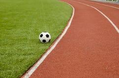 Το ποδόσφαιρο είναι στο τεχνητό γήπεδο ποδοσφαίρου χλόης Στοκ εικόνες με δικαίωμα ελεύθερης χρήσης