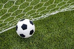 Το ποδόσφαιρο ποδοσφαίρου με το δίχτυ στο τεχνητό πράσινο γήπεδο ποδοσφαίρου χλόης Στοκ Φωτογραφία