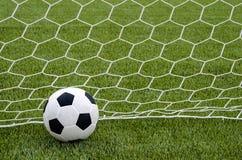 Το ποδόσφαιρο ποδοσφαίρου με το δίχτυ στο τεχνητό πράσινο γήπεδο ποδοσφαίρου χλόης Στοκ εικόνες με δικαίωμα ελεύθερης χρήσης