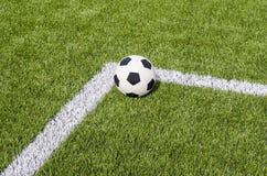 Το ποδόσφαιρο ποδοσφαίρου στην άσπρη γραμμή στον τεχνητό πράσινο τομέα χλόης Στοκ Εικόνες