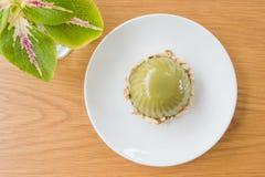Το πράσινο επιδόρπιο γίνεται από το πράσινο τσάι με την κόκκινη κόλλα φασολιών Σε ένα άσπρο πιάτο στον πίνακα Στοκ φωτογραφίες με δικαίωμα ελεύθερης χρήσης
