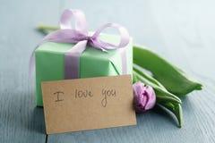 Το πράσινο κιβώτιο δώρων με το πορφυρό τόξο και η τουλίπα στο μπλε ξύλινο υπόβαθρο με το ι σας αγαπούν ευχετήρια κάρτα Στοκ εικόνες με δικαίωμα ελεύθερης χρήσης